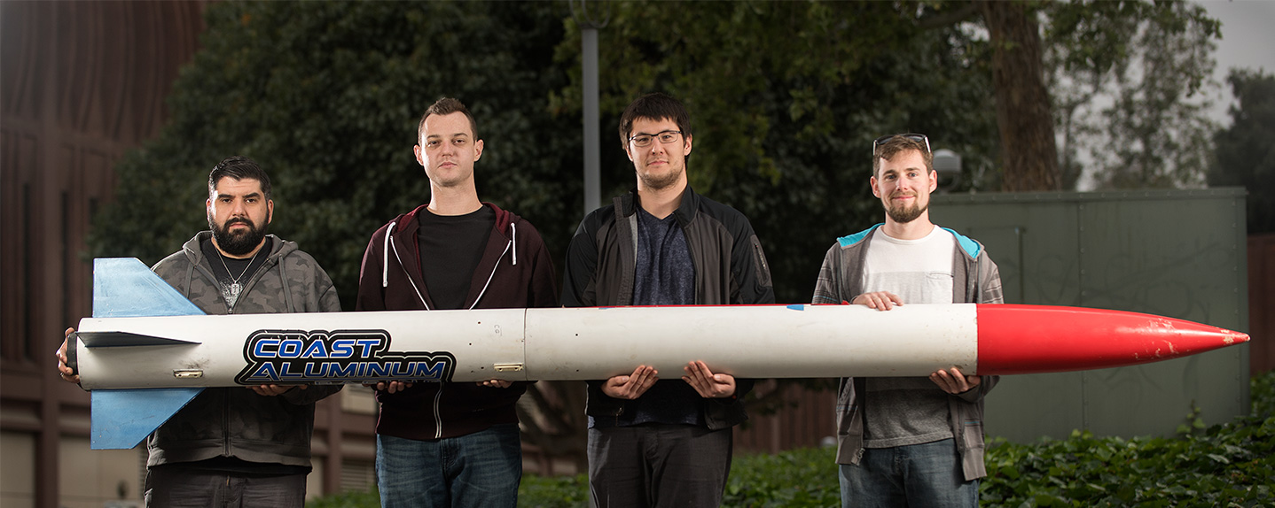 Cal Poly Pomona Rocketry Students holding the Bronco 1 rocket