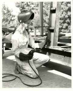 A student welds a portion of a rose float in the mid 1980's.