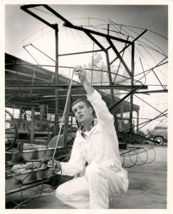 """A student measures a portion of of the metal frame of the 1951 rose float """"College Barn Dance."""""""