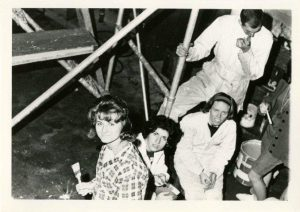 """Students painting portions of the 1964 float """"Cutting The Apron Strings."""""""