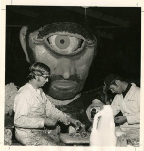 "Two students work on the 1973 float ""Monster Matinee"" as a giant Cyclops peers over them."