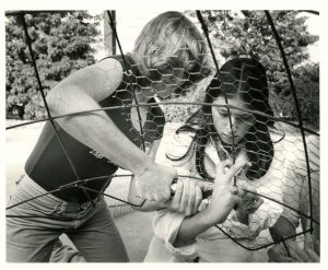 Two women work on the wireframe of a float in the 1970's.