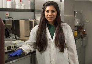 Cinthia Ayala wearing a lab coat inside a lab room