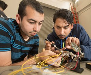 Andres Colon and Brian Tapia, both electrical engineering students, solder connections for the sensors.